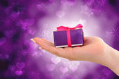 Female hand holding purple gift on starry heart background — Stok fotoğraf