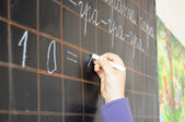Child hand writing on blackboard — Stok fotoğraf