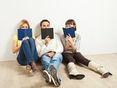 Three amused friends with books — Stock Photo