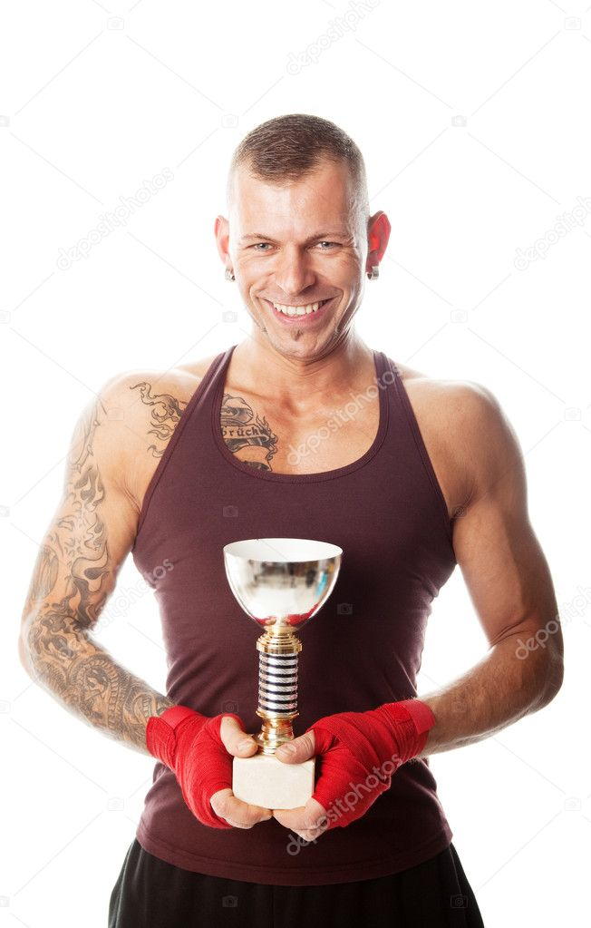 Muscular sportsman holding his chamption cup; isolated on white — Stock Photo #4784649
