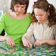 Girl and mom doing puzzle — Stock Photo