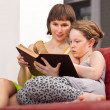 Girl and mom reading book — Stock Photo