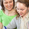 Girl doing homework with her mom - Stock Photo