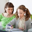 Girl doing prework with her mom - Stock Photo