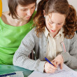Girl doing homework with her mom — Stock Photo
