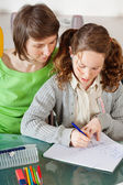 Girl doing homework with her mom — Стоковое фото