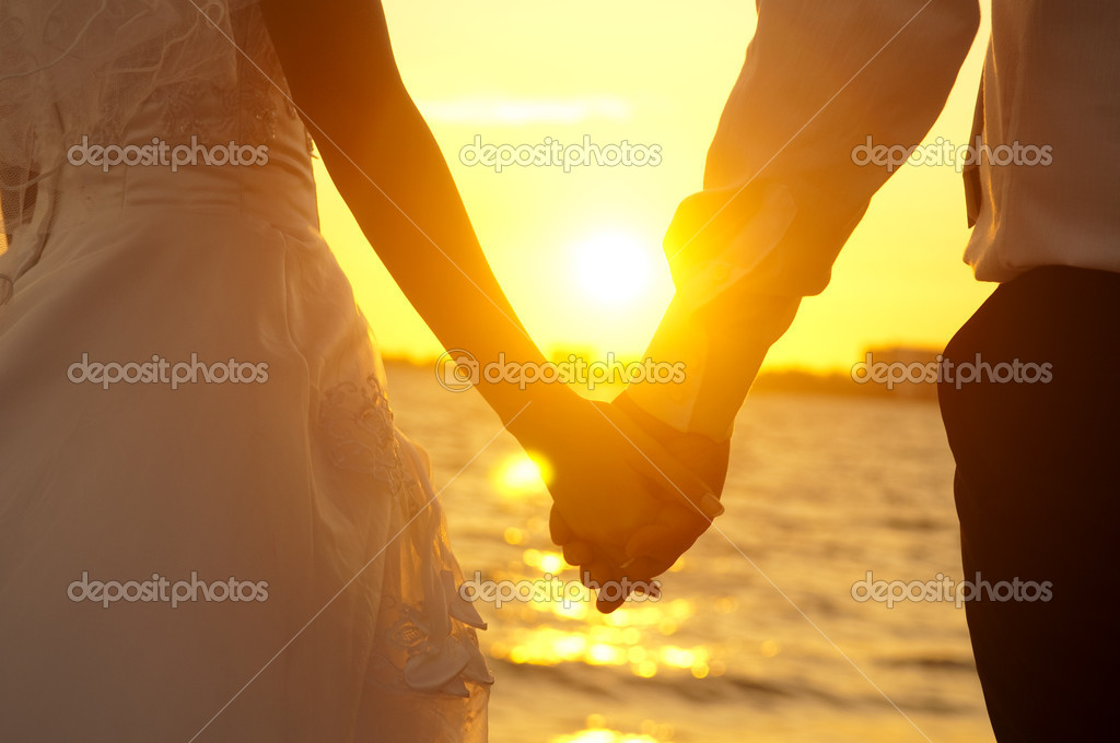 Young adult male groom and female bride holding hands on beach at sunset. — Stock Photo #4403946