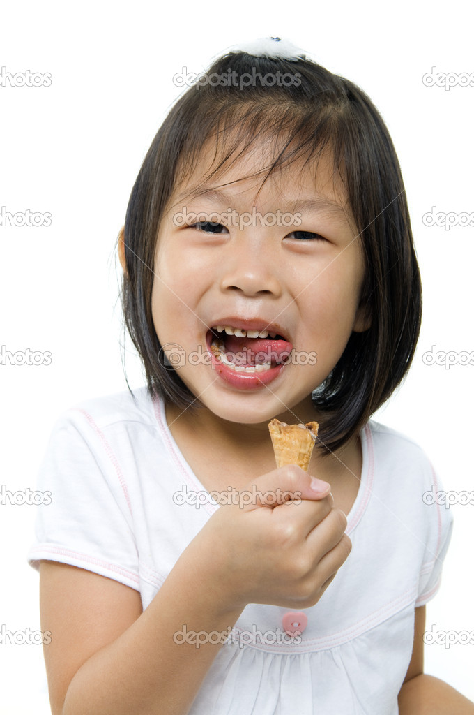 Little Asian girl licking her lips with an ice cream cone in hand. — Stock Photo #4517714