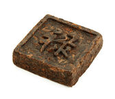 Pressed briquette of green tea with hieroglyphic on white backgr — Stock Photo