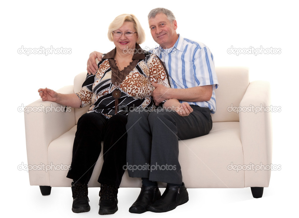Mature couple sitting on a sofa on a white background — Stock Photo #4808692