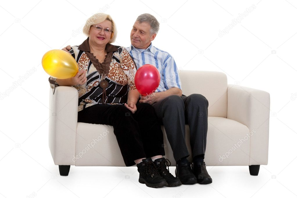 Mature couple sitting on a sofa on a white background — Stock Photo #4866055