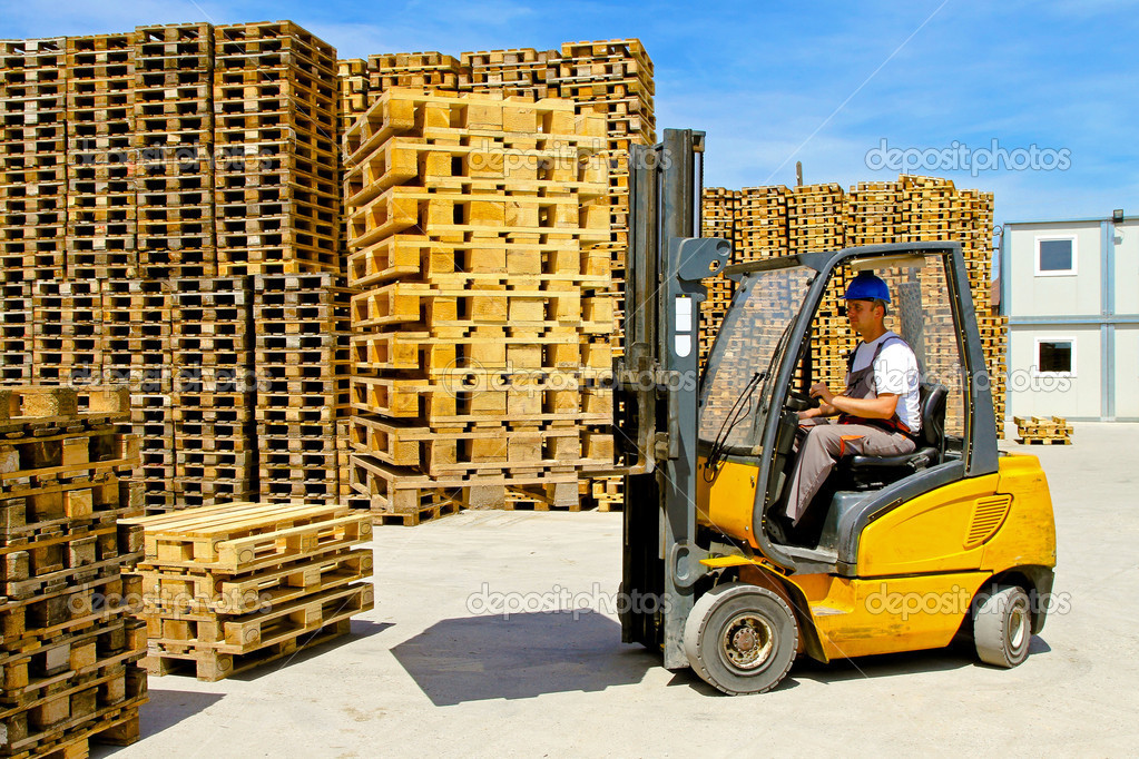 Man operating forklift lifting inside of pallet warehouse — Stock Photo #4412877
