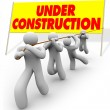 Under Construction - Team Pulling Up Sign — Stock Photo #4440141