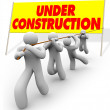 Under Construction - Team Pulling Up Sign - Stock Photo
