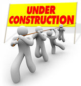 Under Construction - Team Pulling Up Sign — Stock Photo
