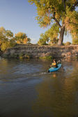 Kayaker paddling across a river — Stock Photo