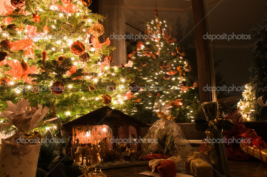 Well lit Christmas tree with presents, nativity scene and outside tree — Stock Photo #4550485