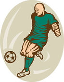 Soccer player running and kicking the ball — Stock Photo