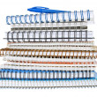 Stack of spiral notebooks with a blue pen - Stock Photo