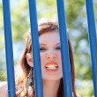 Young caucasiteen girl snarling through bars — Stock Photo #4161733