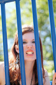 Young caucasian teen girl snarling through bars — Stock Photo