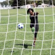 Young black womkicking soccer ball into net — Zdjęcie stockowe #4193948