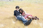 Young teen couple reclining outdoors in yellow grass — Stock Photo