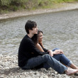 Teen couple sitting on stony river bank — Stock Photo