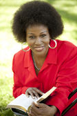 Middle-aged Black woman outdoor reading Bible smile — Stock Photo