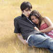 Young teen couple reclining in yellow grass — Stock Photo