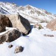 Stock Photo: Boulders, stones in snow with green grass. Caucasus mountains.