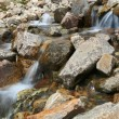 Flowing glacier stream among stones. Caucasus mountains. — Stock Photo