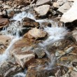 Foto Stock: Flowing glacier stream among stones. Caucasus mountains.