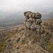 Rock column against valley in fog.Crimea mountains. — Stock Photo