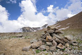 Heap (pyramid) of stones,Caucasus mountains,clouds — Stock Photo