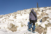 Climber in snowshoes (snow shoes) walking at the mountain slope. Russia. Ur — Stockfoto