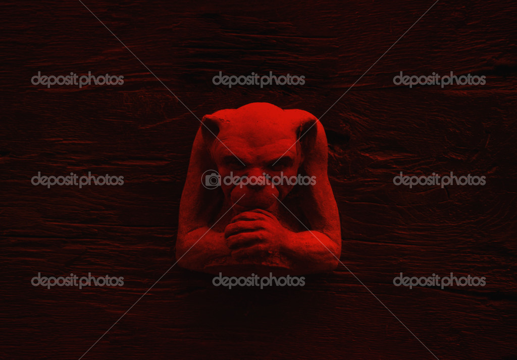 Stone carved gremlin figure on wood surface in red light — Stock Photo #4098294