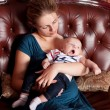 Mother with Her Yawning Baby on Sofa — Stock Photo #4122529