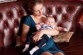 Matka s dítětem na pohovce — Stock fotografie