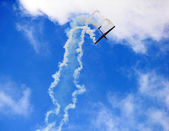 Airplane high in the sky with trailing smoke. — Stock Photo