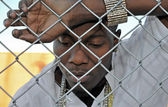 Sad African American man leaning against a fence. — Stock Photo