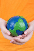 Children's hands holding a globe — Stock Photo