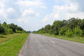 Long country road with white lines in the centre — Stock Photo