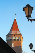 Red tower and street lamps on the backgrounf of blue sky — Stock Photo