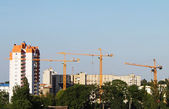 Cranes and building on a background blue sky — Stock Photo