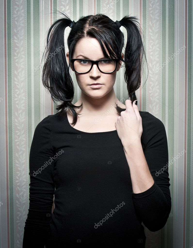 A young nerd girl with ponytails and large glasses  Foto Stock #5097623