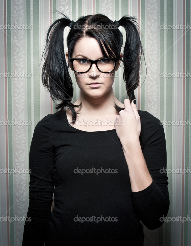 A young nerd girl with ponytails and large glasses  Stockfoto #5097623