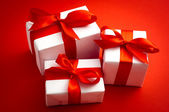 Three white gift boxes over red background — Stock Photo