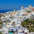 Traditional windmills in village Oia in Santorini, Greece - Stock Photo