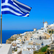 beautiful oia windmill with national flag of greece — Stock Photo